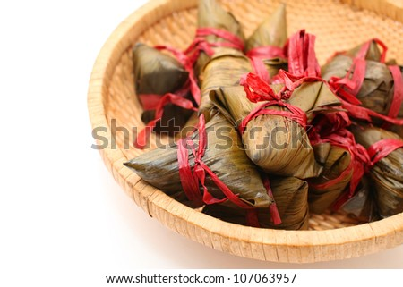 Rice dumplings on basket isolated on white - stock photo