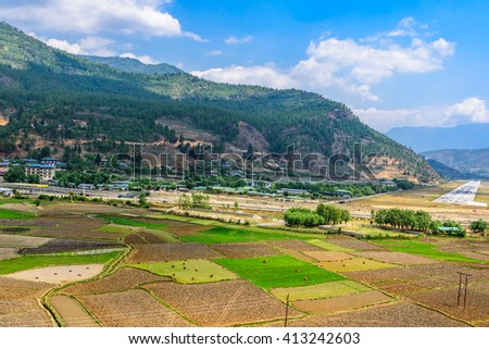 Rice field,mountain view and airport in Bhutan - stock photo