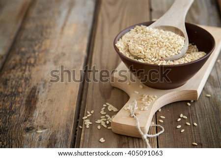 Rice grains in a spoon on a wooden table - stock photo