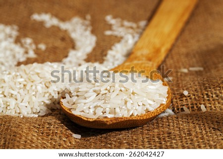 rice grains on a wooden spoon   - stock photo
