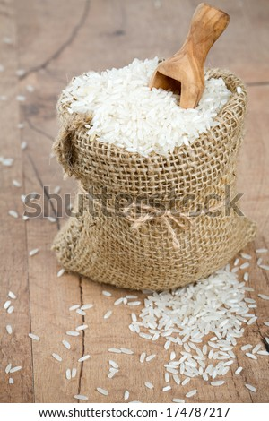 rice in a burlap bag on wooden surface - stock photo