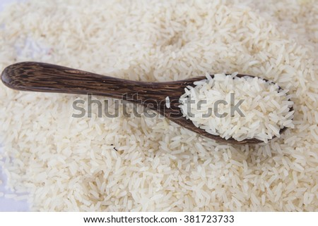 rice in a wooden spoon - stock photo