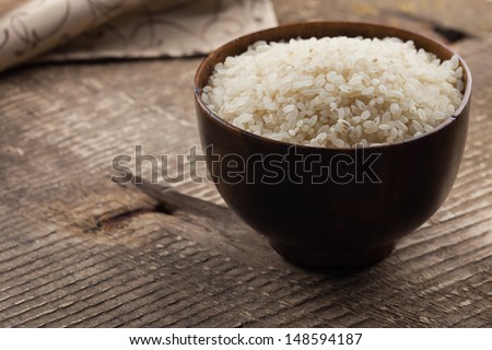 Rice in bowl on wooden background. Selective focus. - stock photo