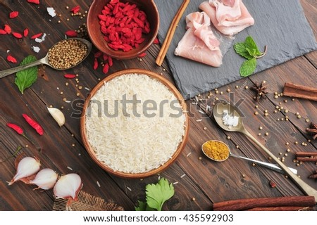 Rice, ingredients and kitchen utensils for cooking on wooden background. - stock photo