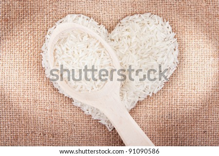 Rice laid out in a heart shape on sackcloth with a wooden spoon - stock photo