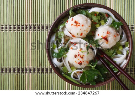 rice noodle soup with fish balls on a bamboo table. top view of a horizontal  - stock photo