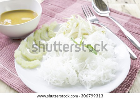 Rice noodles in (with) fish curry sauce / Traditional Thai cuisine, rice vermicelli served and vegetable on wood table.Selective Focus. - stock photo