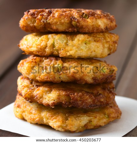 Rice patties or fritters made of cooked rice, carrot, onion, garlic and celery stalks arranged in a pile, photographed with natural light (Selective Focus, Focus on the front of the patties) - stock photo
