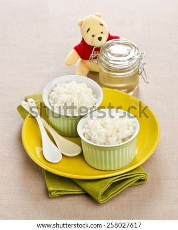 rice porridge with honey for children in small ceramic bowls with a toy bear in the background - stock photo