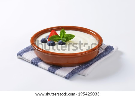 rice pudding with blueberries and strawberries, served in the ceramic bowl with blue linen - stock photo