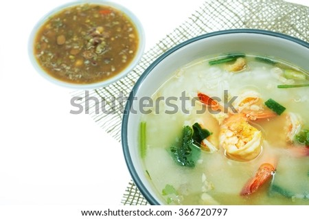 Rice soup with fried garlic and shrimp. On burlap background. With sauce made from  salted soybean mix with chili  on white background. Shallow depth of field. - stock photo