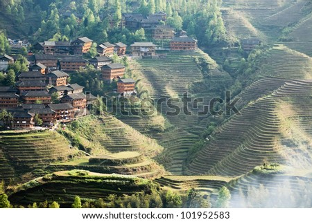 rice terraces and ethnic minority village at dusk in guangxi province,China - stock photo