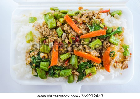 Rice topped with stir fried minced pork and basil in foam box. Thai food - stock photo