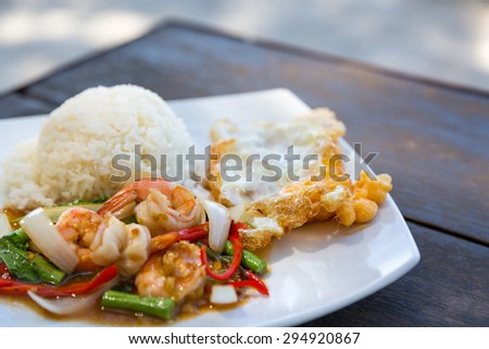 Rice topped with stir-fried shrimps and basil Thai style ( Kra prao gai ) on wooden table - stock photo