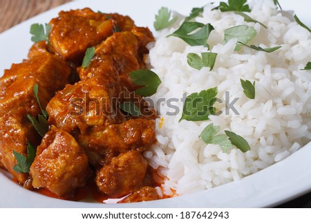 Rice with chicken curry and herbs closeup on plate horizontal.   - stock photo