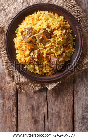 Rice with meat and vegetables on an old table close-up. vertical view above, rustic style  - stock photo