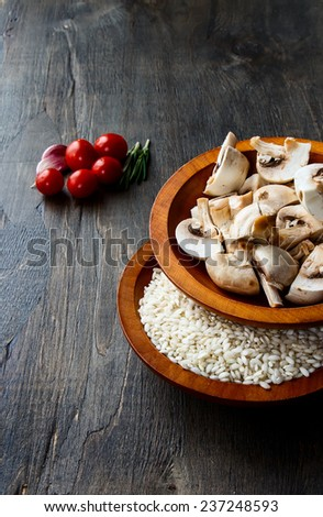 Rice with raw vegetable for cooking on wood texture, selective focus - stock photo