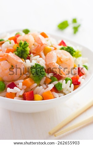 Rice with vegetables and shrimps on white background - stock photo