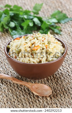 rice with vegetables in a ceramic bowl on a mat woven background - stock photo