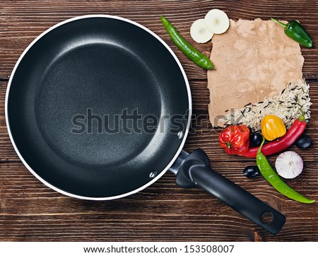 rice with vegetables next to a frying pan and paper for recipe - stock photo