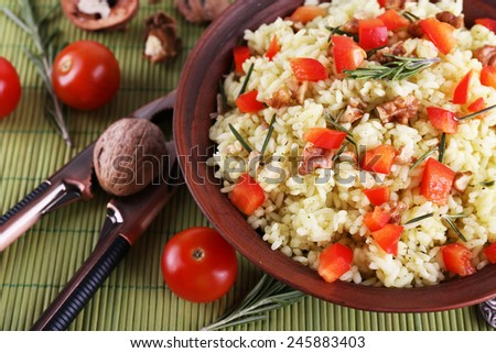 Rice with walnuts and cherry tomatoes in plate on bamboo mat background - stock photo
