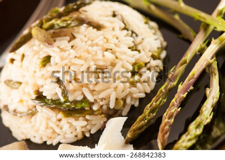 Rice with wild asparagus on a blavk plate with fork served on a wooden table - stock photo