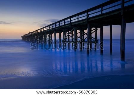 Rich blue sunrise ocean beach pier motion blur - stock photo