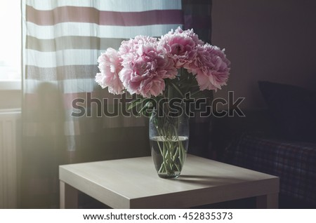 Rich bouquet of pink peony roses flowers in vase on table with sunlight background. Summer time concept. Still life, rustic style. Fresh floral, home decor. Place for text, copy space - stock photo