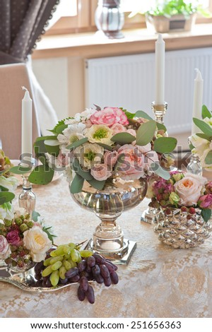 Rich bunch of anemones, tea roses, tulips, in vase on bride and groom table - stock photo