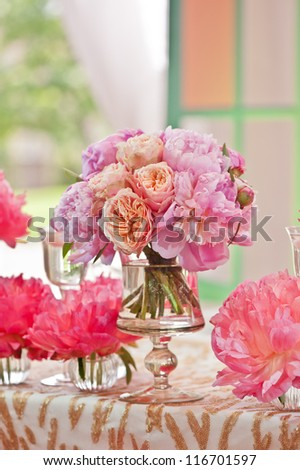 Rich bunch of peonies and tea roses in vase on bride and groom table - stock photo