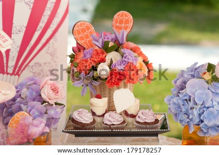 Rich bunch of peonies, tulips, roses in vase on sweet table.  Cupcakes and  berries desserts. - stock photo