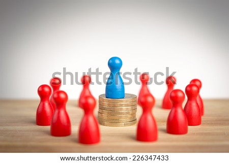 Rich business leader concept with blue figure on top of coin stack as a symbol of wealth  - stock photo