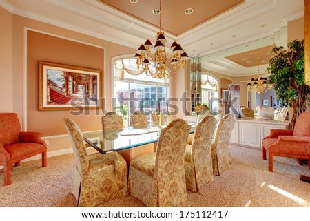 Rich dining room with wonderful dining table set, antique chairs and decorative tree - stock photo