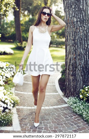 Rich fashionable brunette woman walking in park - stock photo