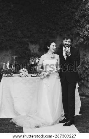 rich stylish happy bride and groom holding hands look at each other near a white wedding table decorated with flowers peonies and candles Rome Italy black and white - stock photo