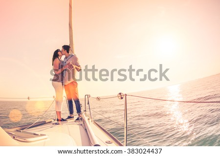 Rich young couple in love on sailboat cheering at sunset - Happy wander lifestyle concept sailing around world - Soft focus on rose quartz filter - Lens flare and tilted horizon as part of composition - stock photo