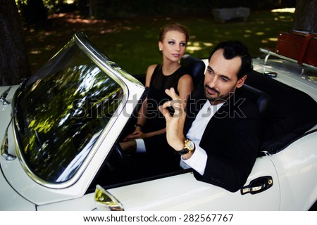 Richly dressed wealthy and famous couple sitting inside cabriolet luxury car, successful man sitting behind convertible steering wheel with its ok hand gesture, happy man and woman enjoying the life - stock photo