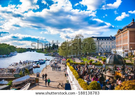 RICHMOND UPON THAMES, UK - APR 19: People enjoy the sunny weather in Richmond Upon Thames near London on April 19, 2014. The town is in proximity of a large number of parks, including Richmond Park - stock photo