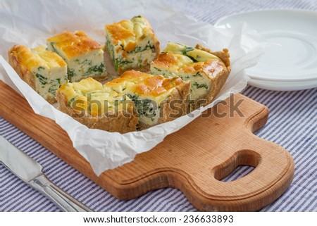 Ricotta and spinach quiche pie pieces on wooden board - stock photo