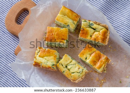 Ricotta and spinach quiche pie pieces on wooden board, top view - stock photo