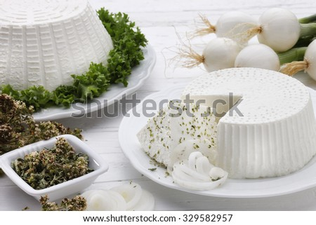 Ricotta cheees on a white dishwith onion, oregano, on white wooden table. - stock photo