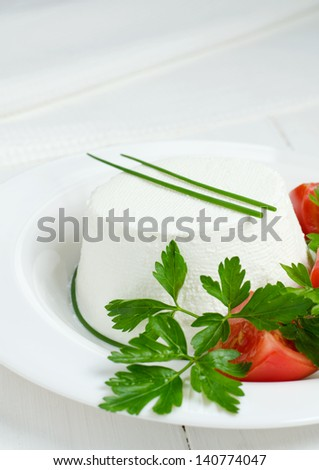 Ricotta cheese with parsley leaves and tomatoes - stock photo