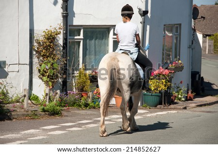 Rider enjoying a quiet hack through a pretty shropshire village - stock photo