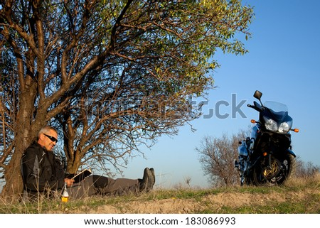 rider is resting under the tree. / motorcycle and man - stock photo