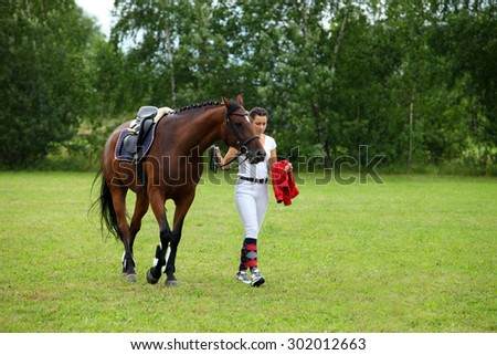 Rider leads horse by bridle across the meadow - stock photo
