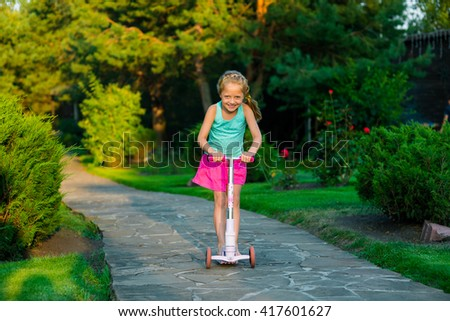 Rider of the scooter had chosen the road made of stone to test her new present. Having a ride in garden. Beautiful caucasian female child. - stock photo