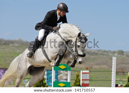 Rider on gray horse in jumping show - stock photo