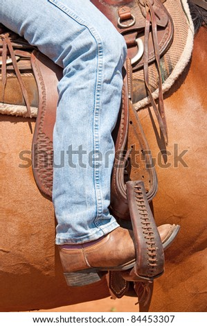 Rider's foot in stirrup in a western saddle - stock photo