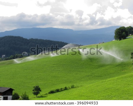 Ridge on alpine pasture with grass sprinklers in South Tyrol near Castelrotto - Italy - stock photo