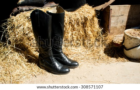 Riding boot in the stable, hay background - stock photo